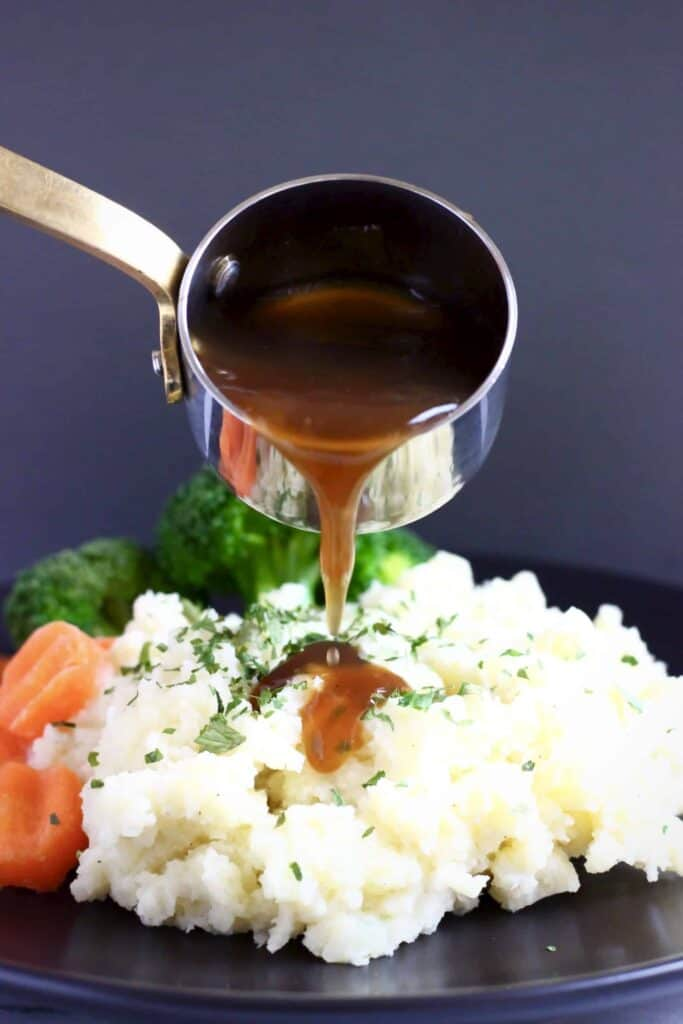 Photo of a pile of mashed potatoes topped with green herbs with sliced carrots and broccoli on a black plate with brown gravy being poured over in a silver saucepan against a dark grey background