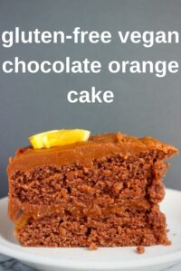 Photo of a slice of chocolate cake topped with an orange slice on a white plate against a grey background