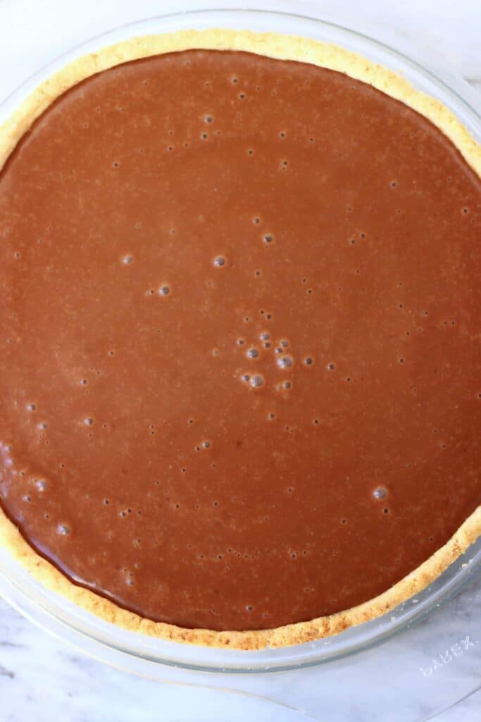 Photo of a cooked pastry crust filled with liquid chocolate ganache in a glass pie dish against a marble background