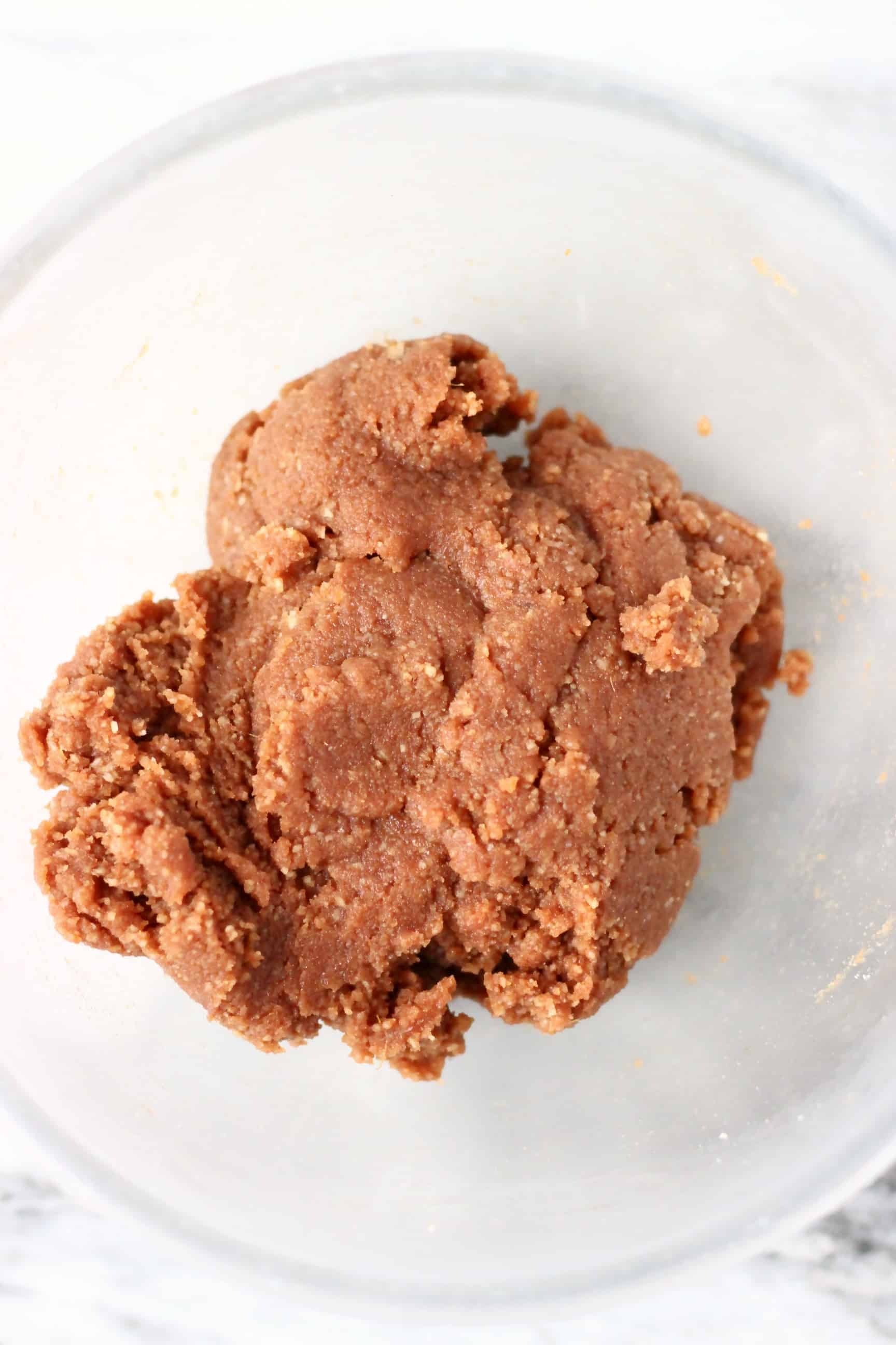 Raw gluten-free vegan gingerbread cookie dough in a glass mixing bowl