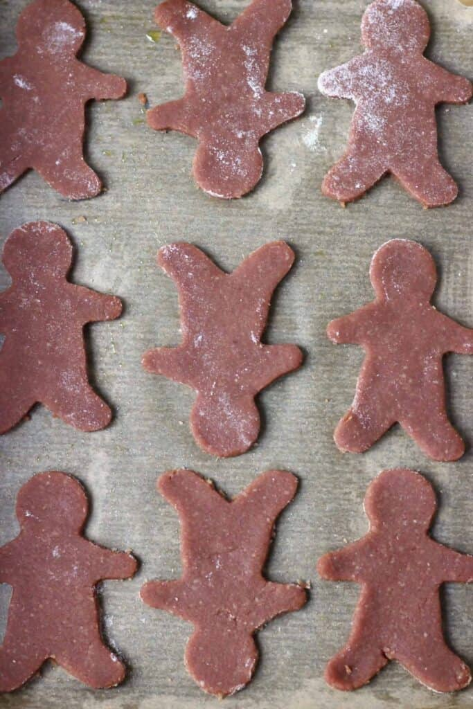 Photo of nine raw gingerbread cookies on a sheet of brown baking paper