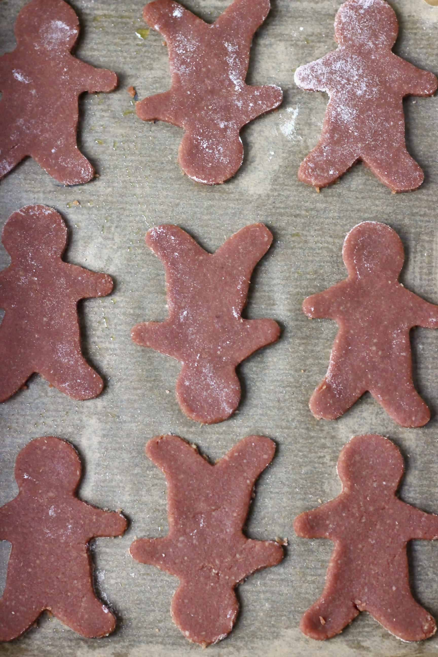 Nine raw gluten-free vegan gingerbread cookies on a sheet of baking paper