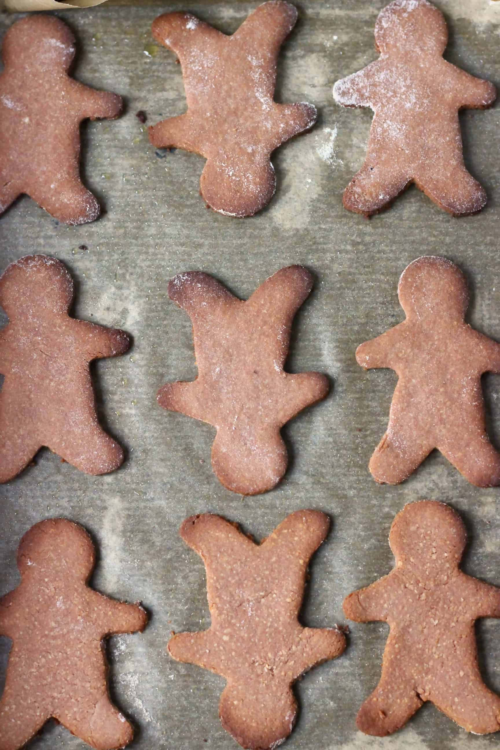 Nine baked gluten-free vegan gingerbread cookies on a sheet of baking paper