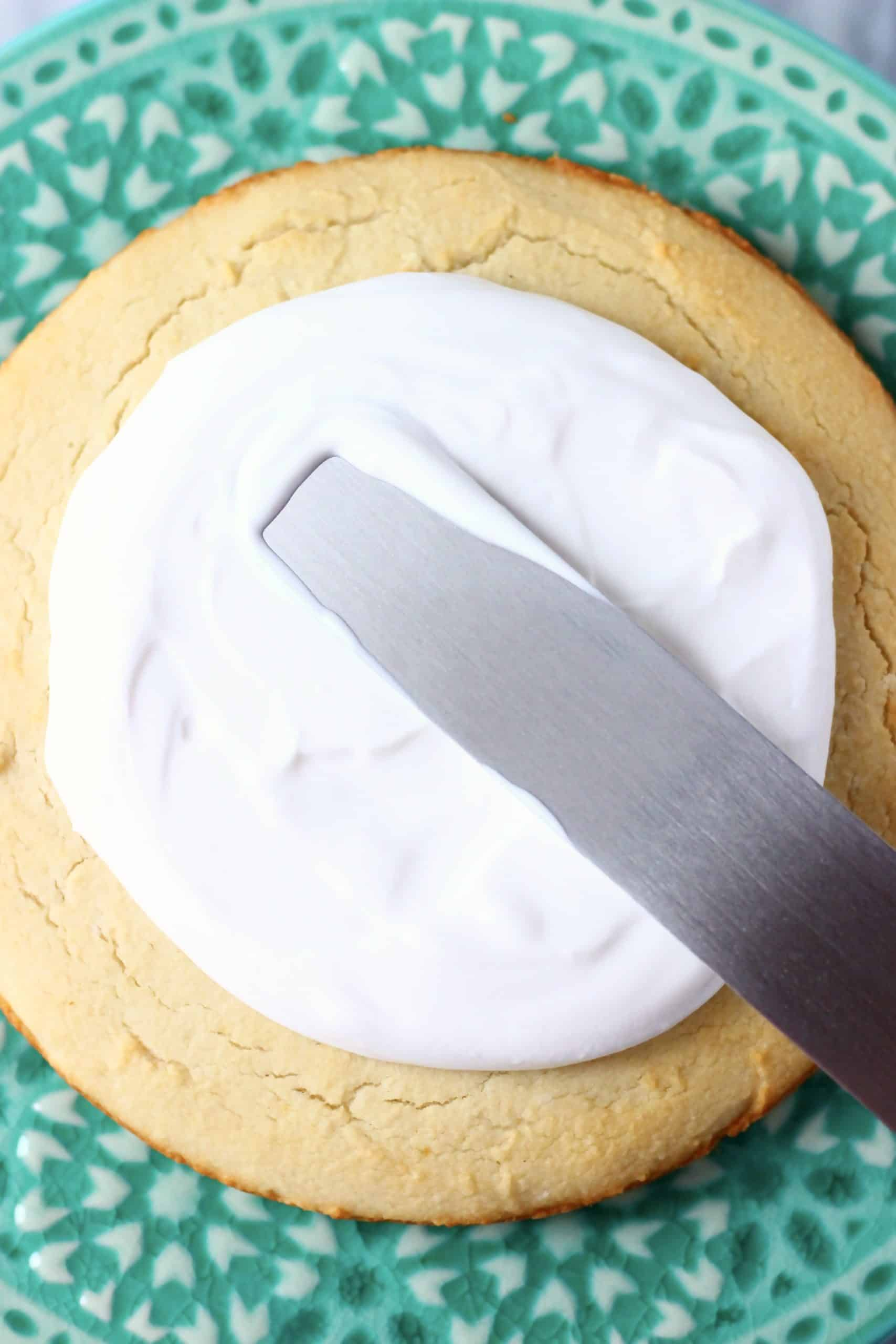 A gluten-free vegan coconut cake sponge on a cake stand being spread with coconut cream frosting with a palette knife