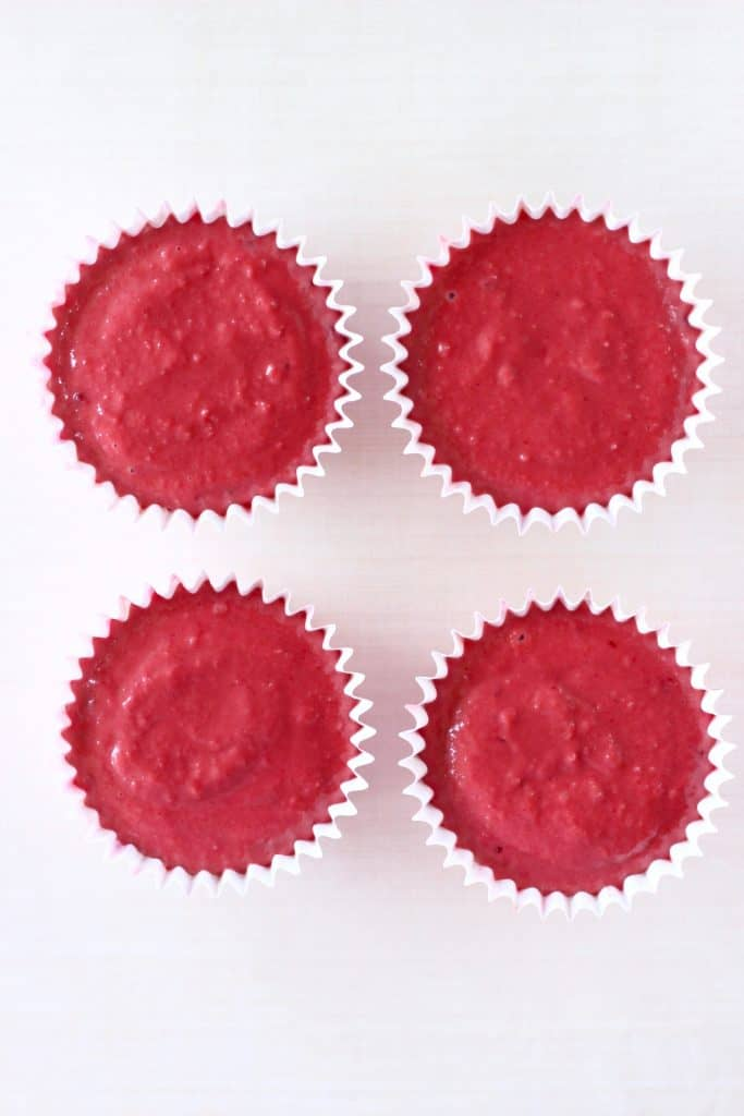 Four cupcake cases filled with raw red velvet cake batter against a white background
