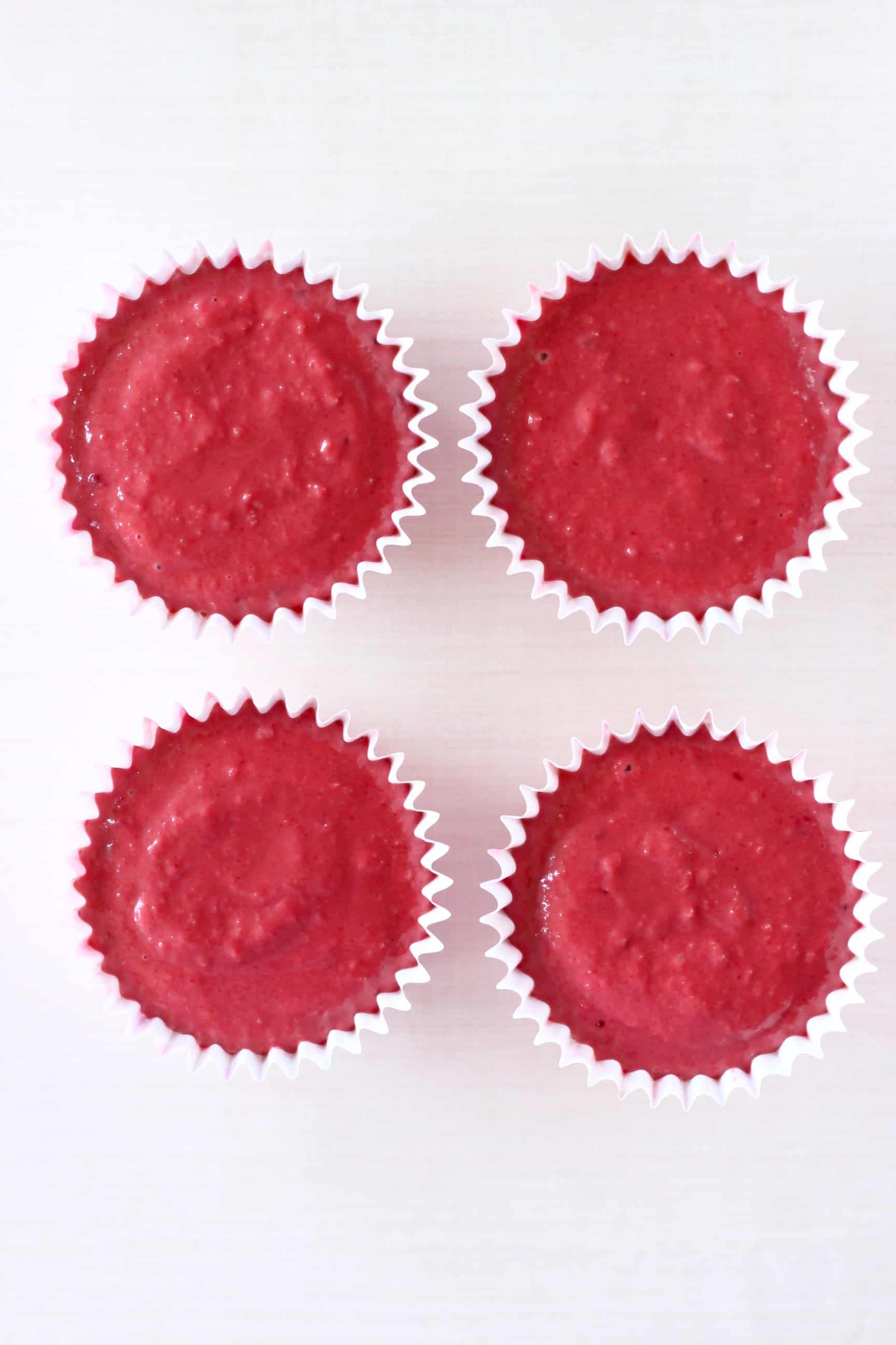 Four cupcake cases filled with raw gluten-free vegan red velvet cupcakes batter