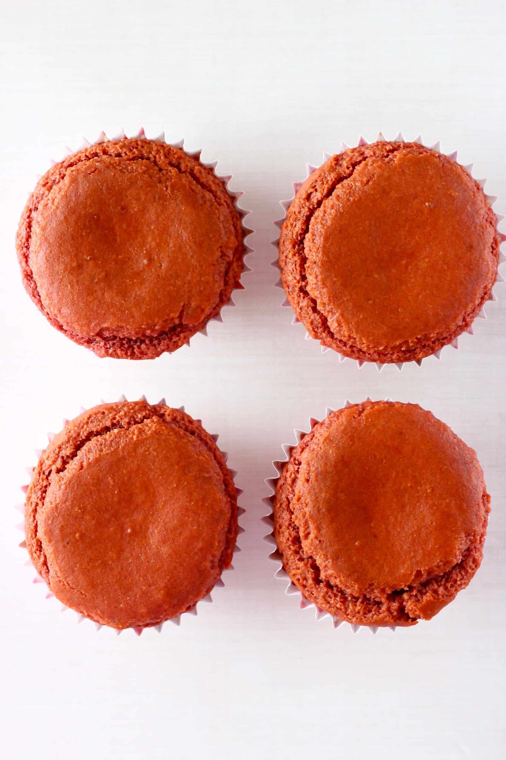 Four gluten-free vegan red velvet cupcakes in cupcake cases