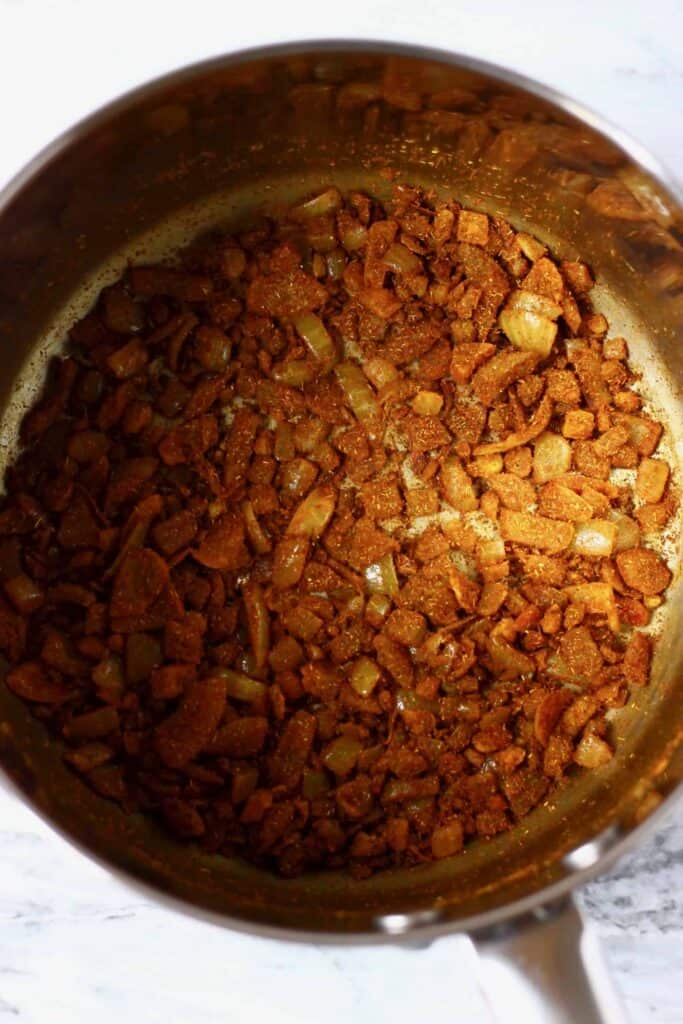 Photo of diced onion with brown spices being fried in a silver saucepan