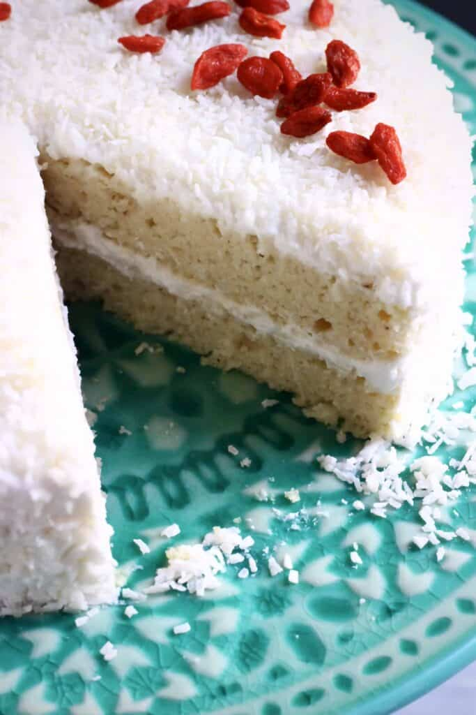 A sliced coconut sponge cake topped with desiccated coconut and red goji berries
