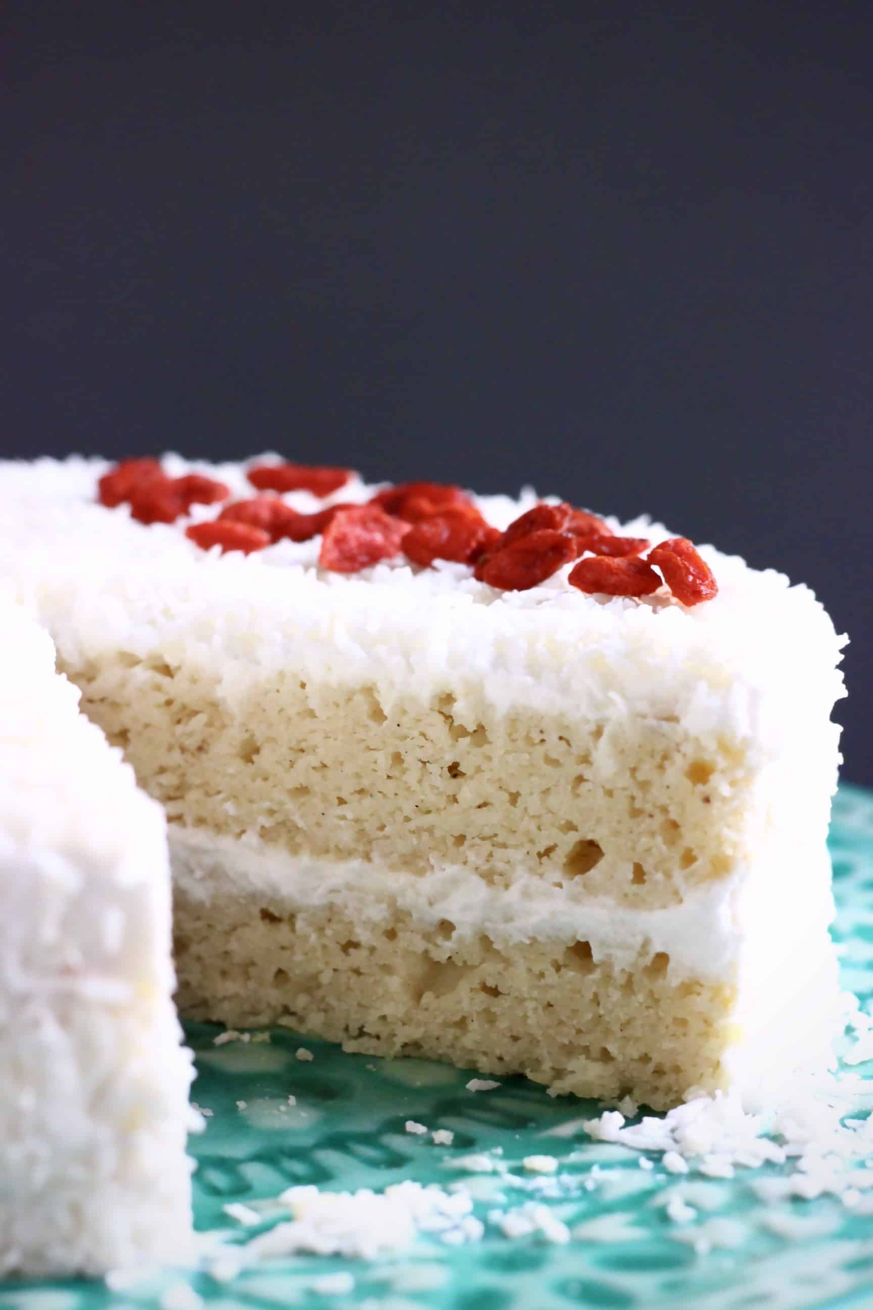 A sliced gluten-free vegan coconut sponge cake topped with desiccated coconut and red goji berries