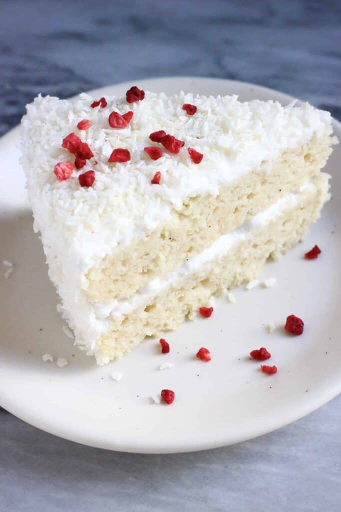 A slice of coconut sponge cake topped with desiccated coconut and freeze-dried raspberries
