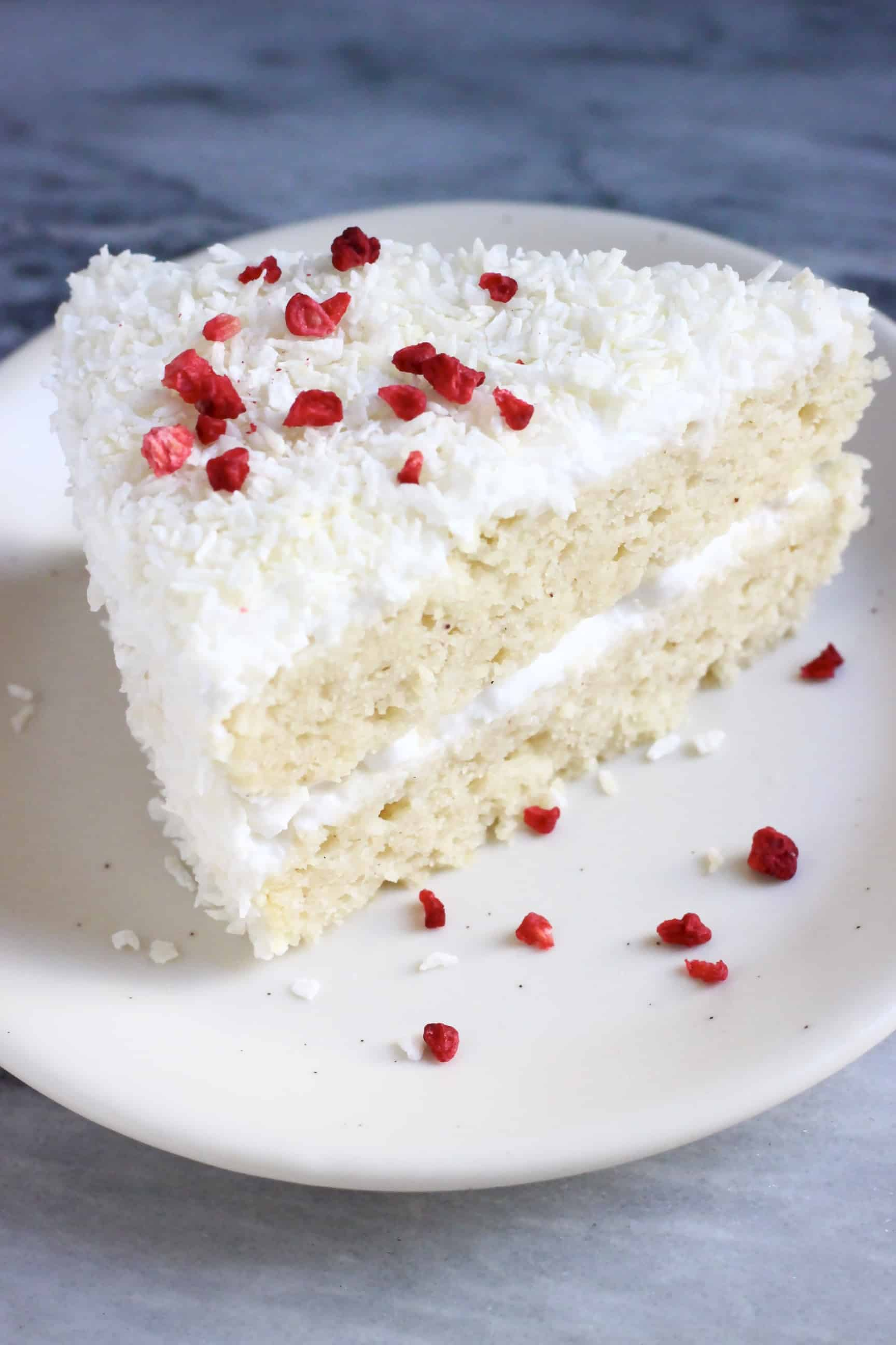 A slice of gluten-free vegan coconut cake topped with desiccated coconut and freeze-dried raspberries