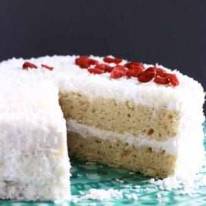 A sliced gluten-free vegan coconut cake topped with desiccated coconut and red goji berries