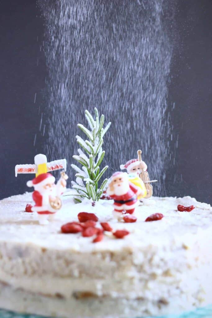 Photo of a fruit cake covered in white buttercream topped with plastic santas against a grey background with icing sugar being dusted over it