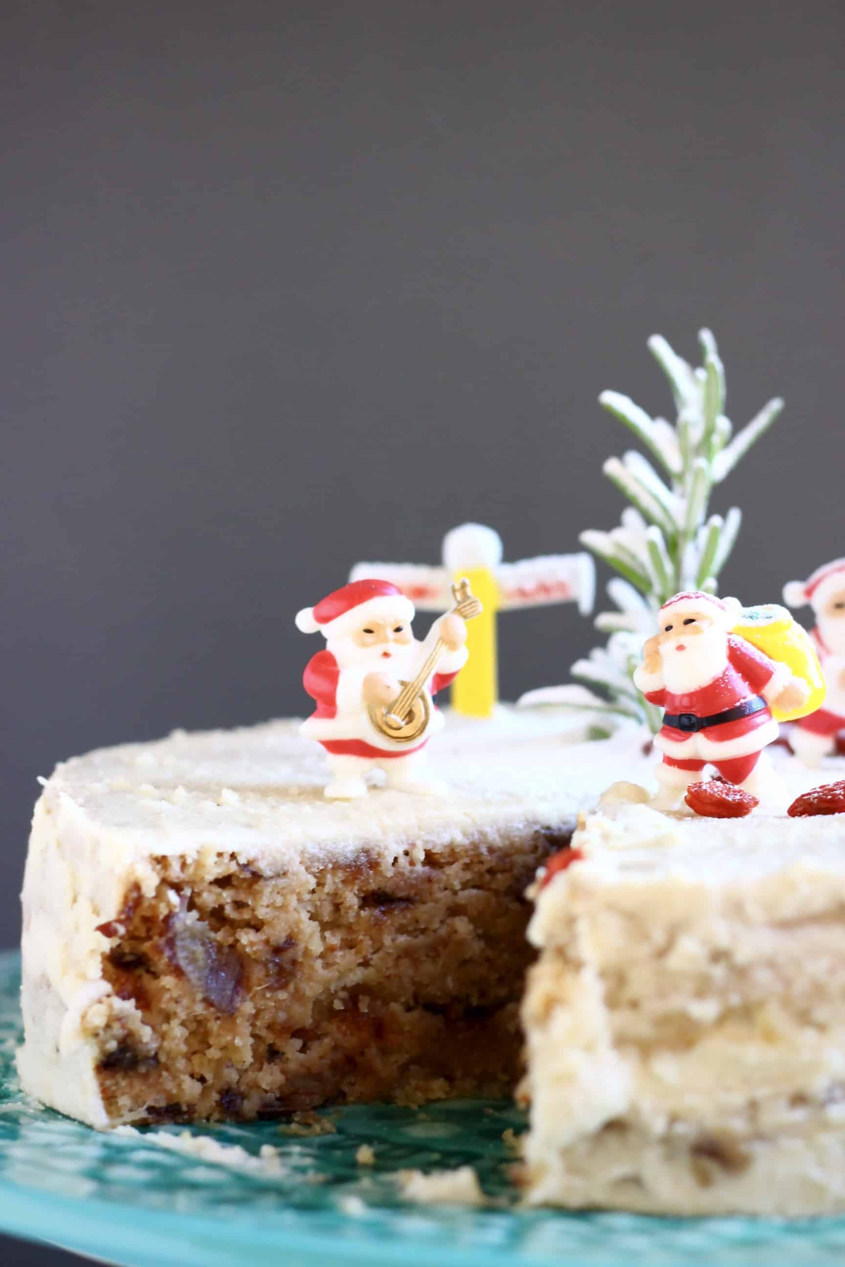 A sliced gluten-free vegan Christmas fruit cake covered in white buttercream and decorated with Christmas decorations