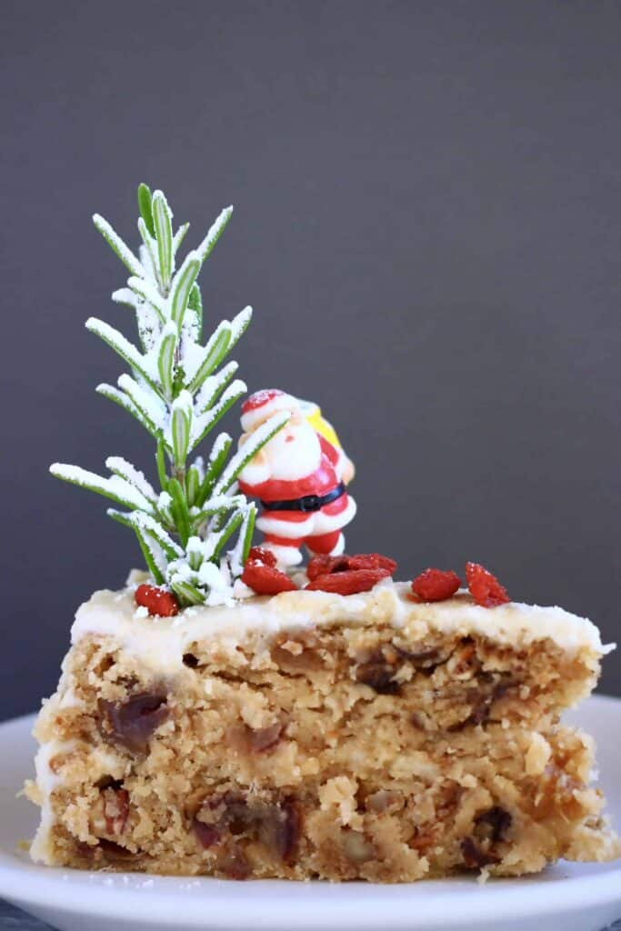 Photo of a slice of fruit cake covered in white buttercream topped with a plastic santa against a grey background