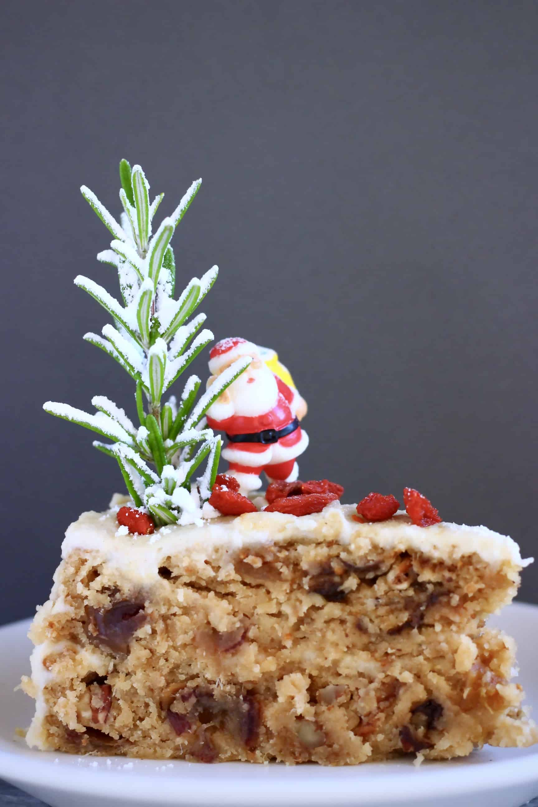 A slice of gluten-free vegan Christmas fruit cake covered in white buttercream topped with a plastic Santa