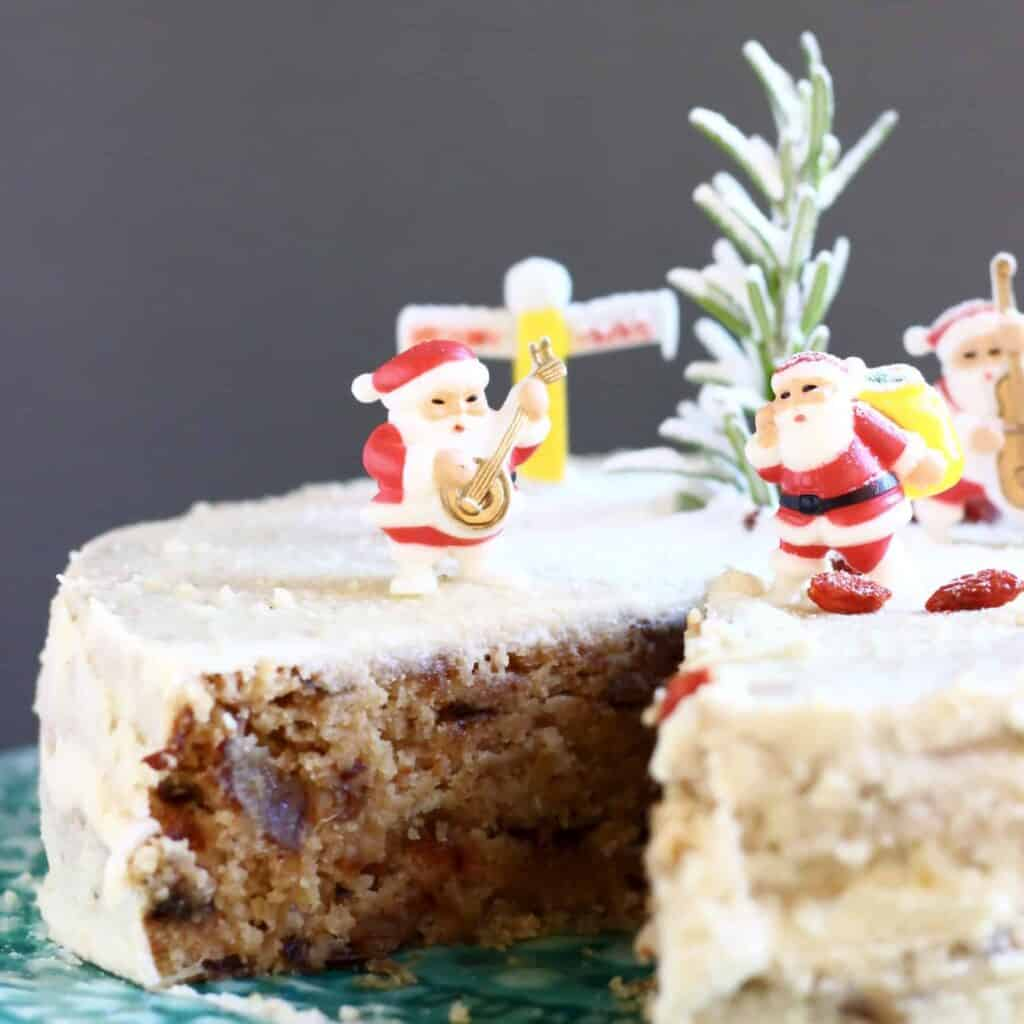 Photo of a fruit cake covered in white buttercream with a slice taken out of it topped with plastic santas against a grey background