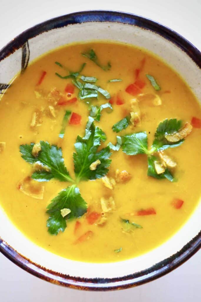 Photo of orange soup topped with green herbs and red chilli in a brown bowl