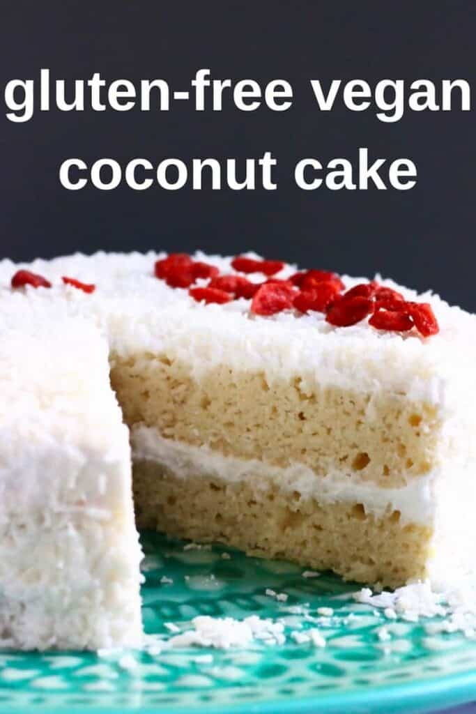 Photo of a sliced coconut cake on a blue cake stand topped with red goji berries