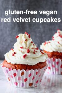 Two red velvet cupcakes topped with white frosting and freeze-dried raspberries on a marble slab against a grey background