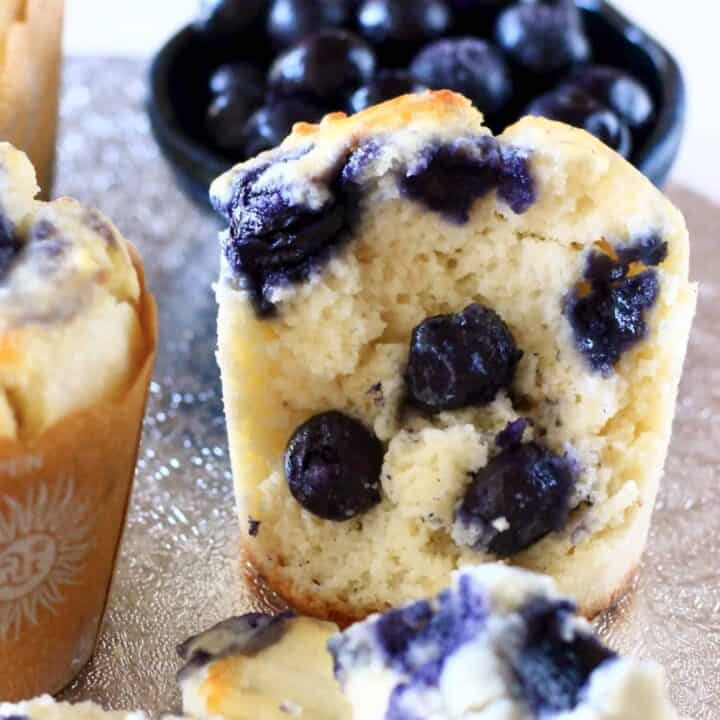 Three vegan blueberry muffins with a bite taken out of one with a bowl of fresh blueberries in the background