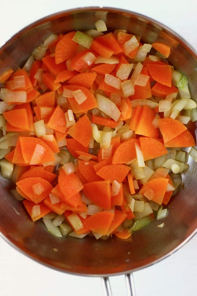 Onion, carrots, garlic and celery being fried in a silver pan