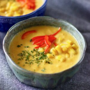 Two bowls of corn chowder against a grey background