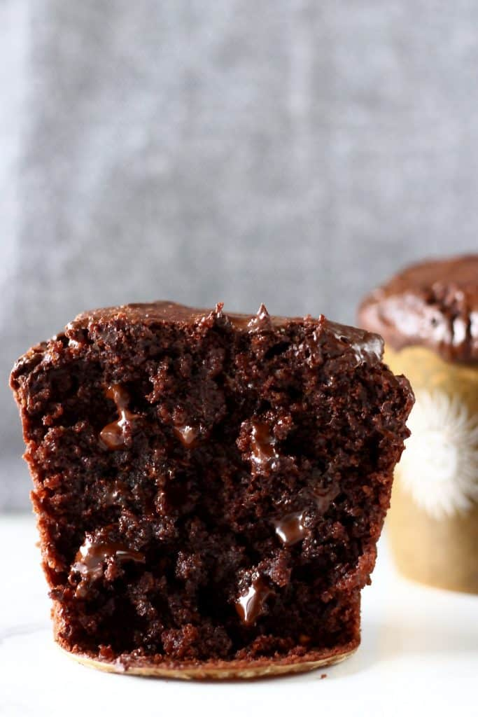 A halved chocolate muffin with chocolate chips against a grey background