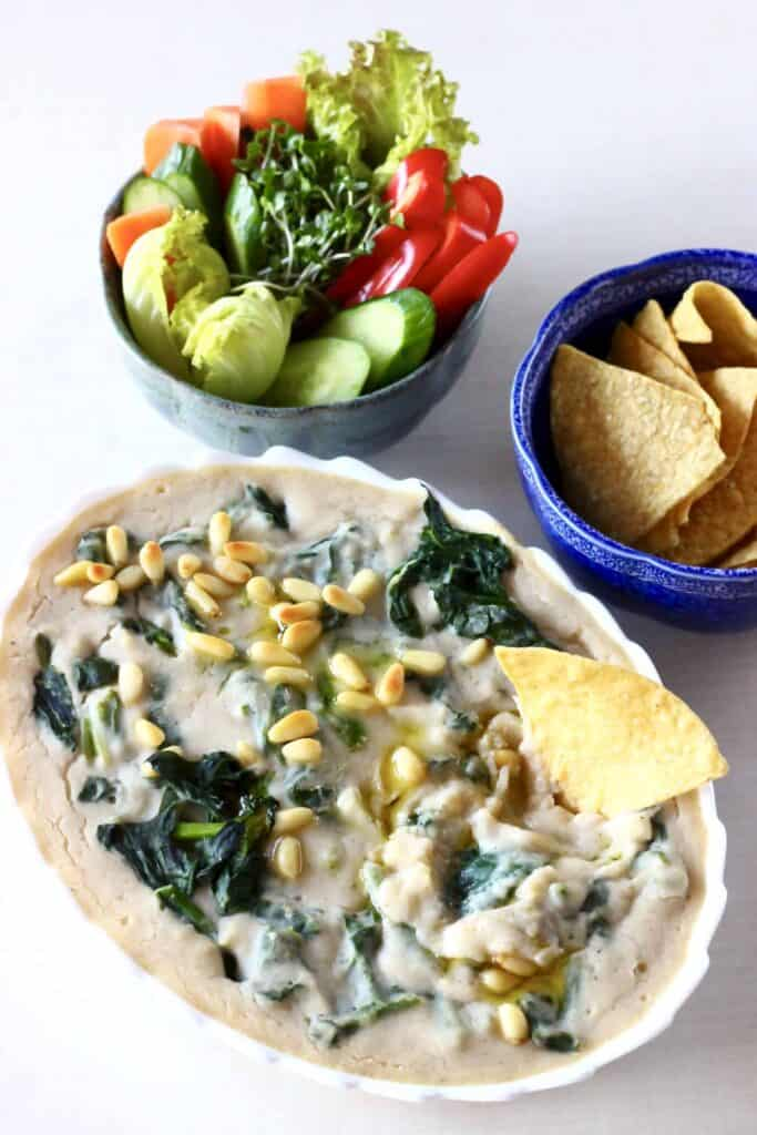 Photo of an oval baking dish filled with creamy spinach and artichoke dip topped with pine nuts with a bowl of tortilla chips and a bowl of vegetable crudités with a tortilla chip sticking into the dip