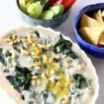Photo of an oval baking dish filled with creamy spinach and artichoke dip topped with pine nuts with a bowl of tortilla chips and a bowl of vegetable crudités