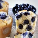 Photo of three blueberry muffins, one with a bite taken out of it, with a bowl of fresh blueberries in the background