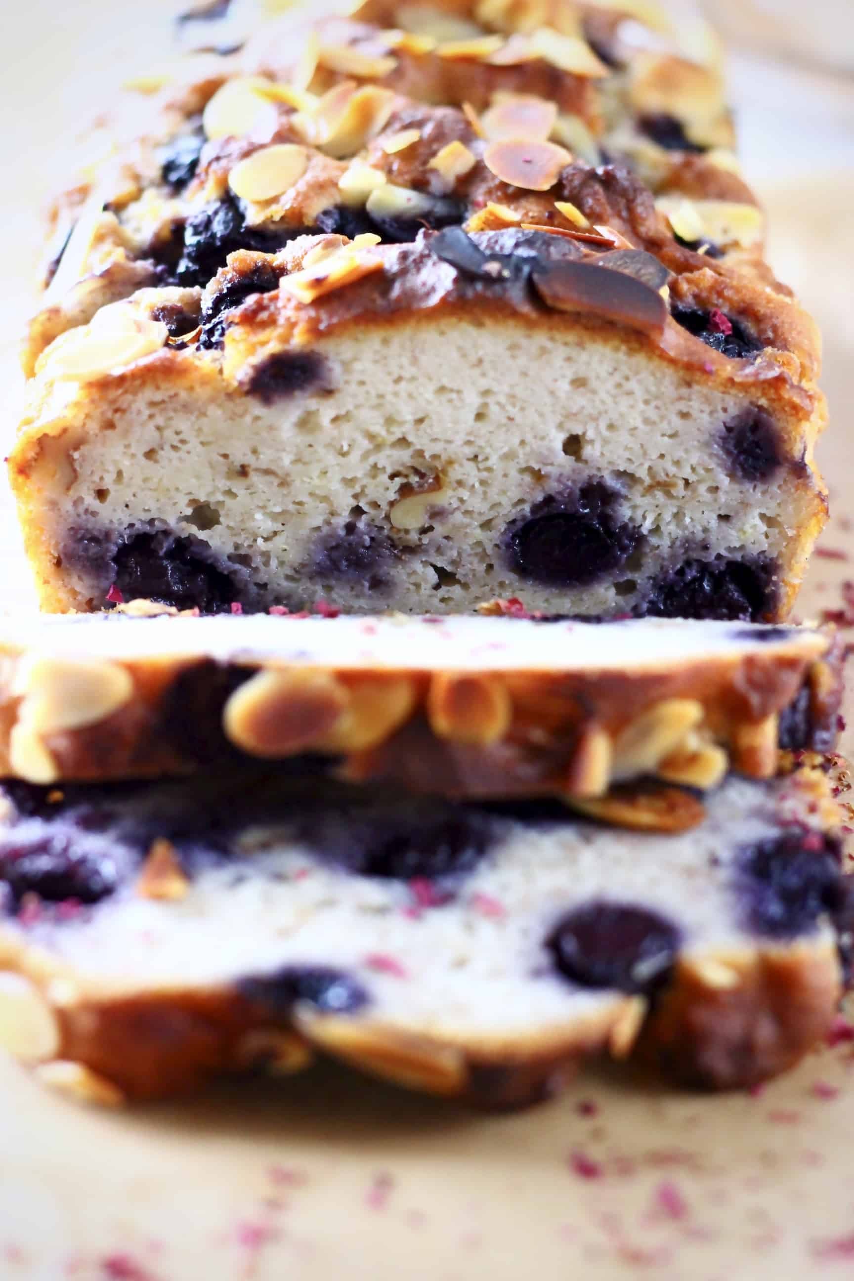 A loaf of gluten-free vegan blueberry banana bread with three slices cut