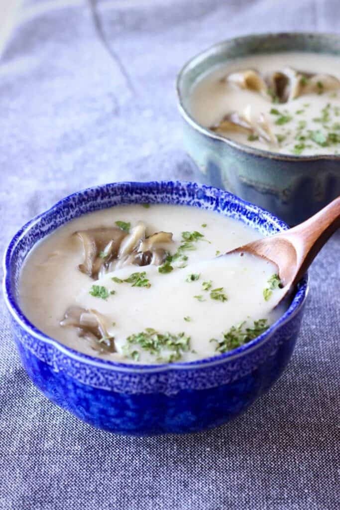 Two blue bowls filled with a beige-coloured mushroom soup with a wooden spoon sticking into one