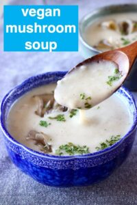 A small dark blue bowl of beige soup with a wooden spoon lifting up a mouthful of it against a grey background
