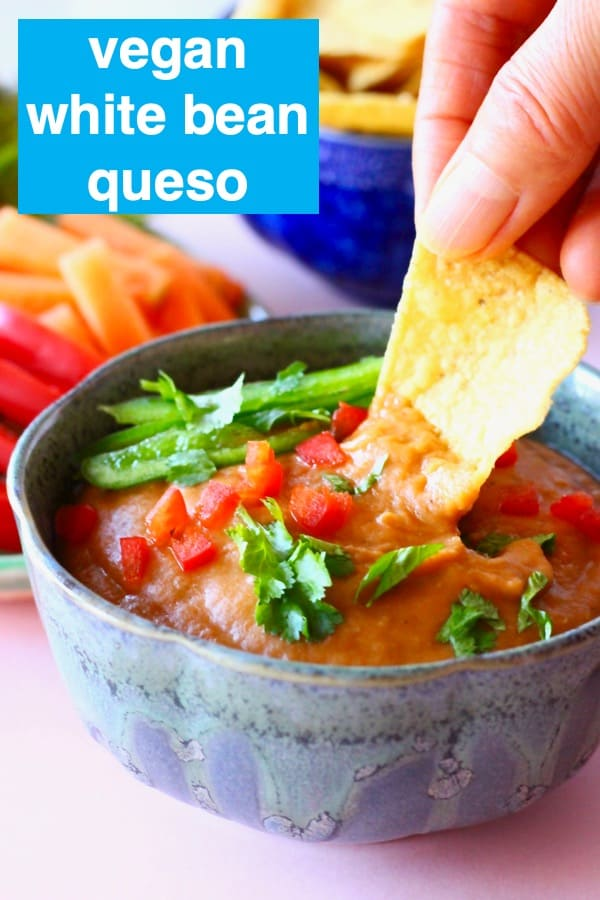 A blue bowl of orange vegan quest topped with green pepper and chopped coriander on a pink background with chopped vegetables and a dark blue bowl of tortilla chips with a tortilla chip being dipped into the quest