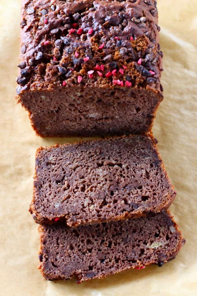 A loaf of chocolate banana bread with two slices on a sheet of brown baking paper