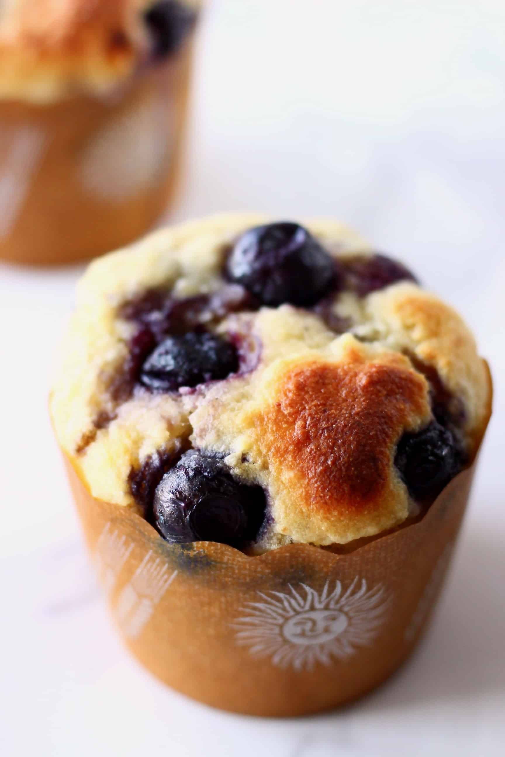 Two gluten-free vegan blueberry banana muffins in brown muffin cases