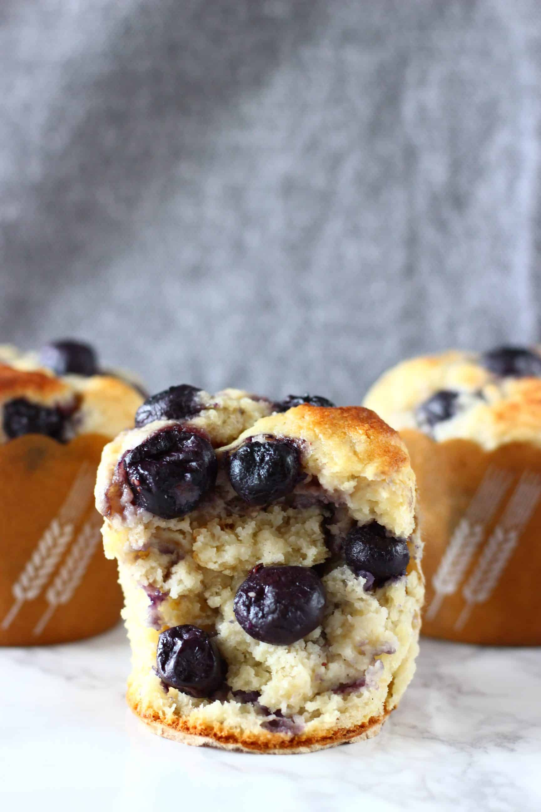 Three gluten-free vegan blueberry banana muffins with one cut in half
