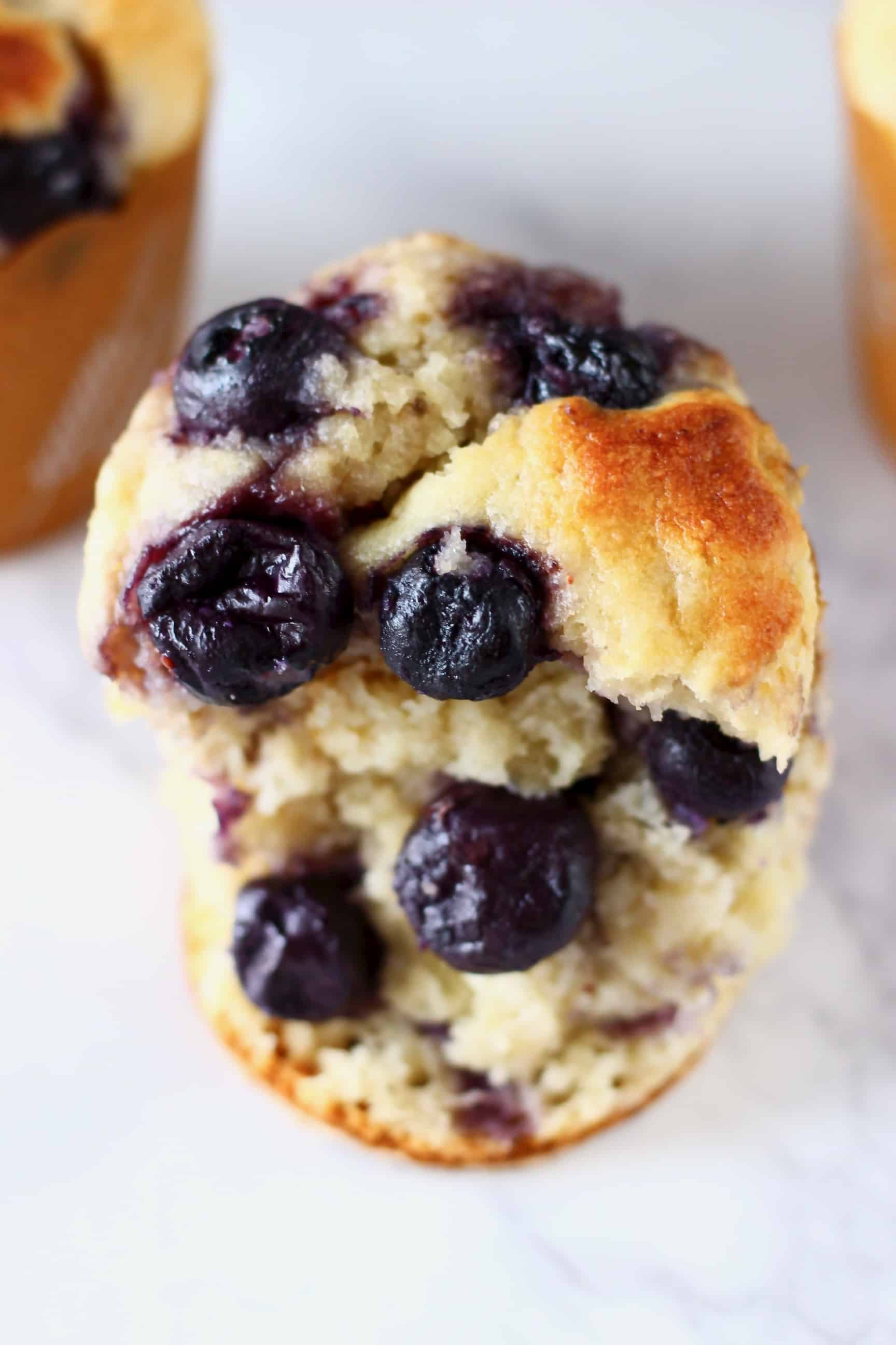 Half a gluten-free vegan blueberry banana muffin with two more muffins in the background