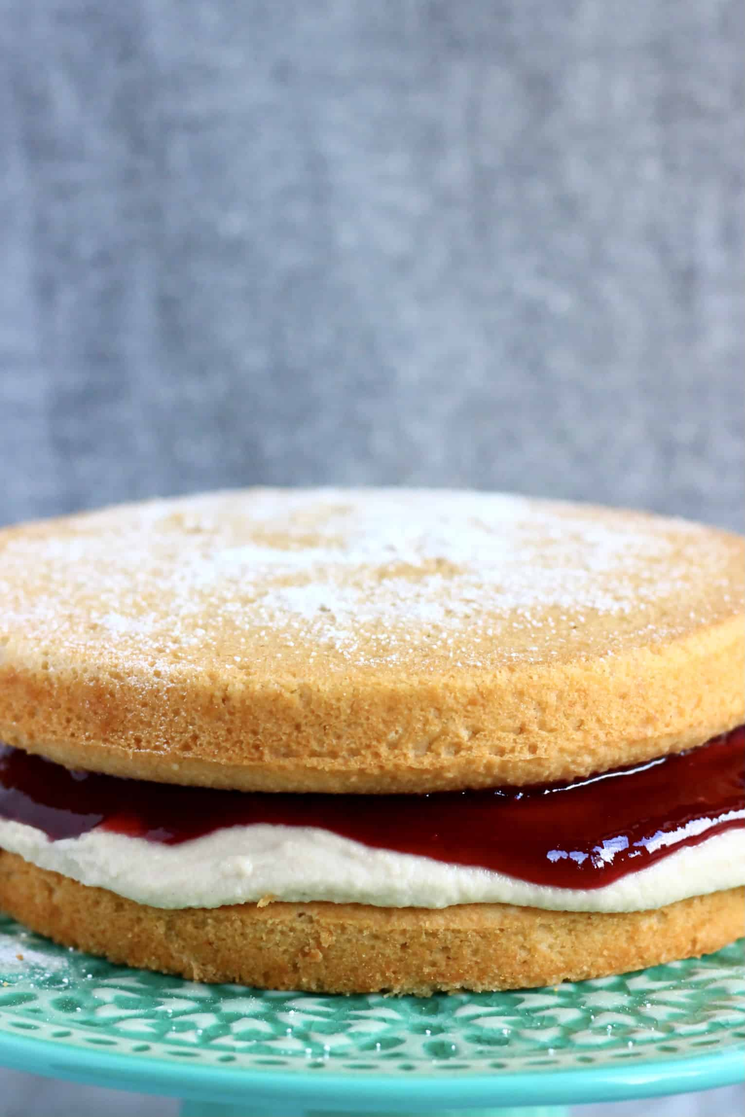 A gluten-free vegan Victoria sponge cake with buttercream and jam on a cake stand