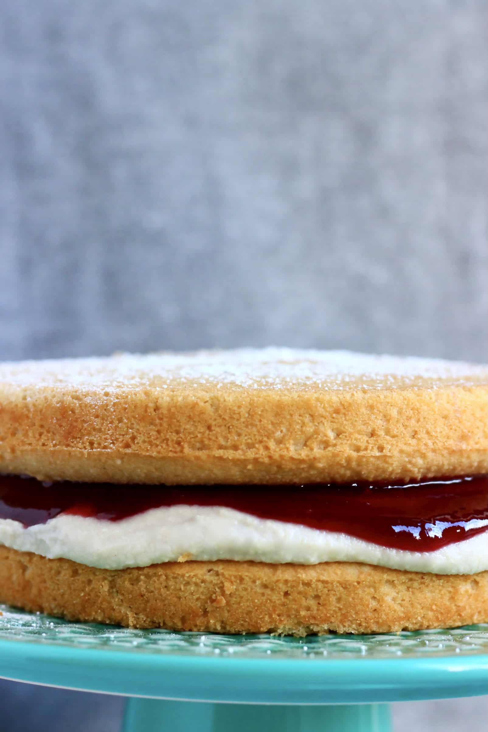 A gluten-free vegan Victoria sponge cake with vegan buttercream and raspberry jam on a cake stand