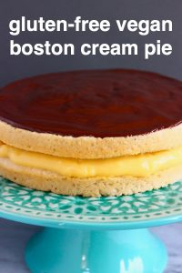 A Boston cream pie on a green cake stand against a grey background