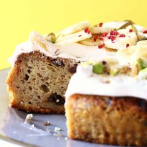 Sliced banana cake with raisins topped with white frosting and sliced bananas