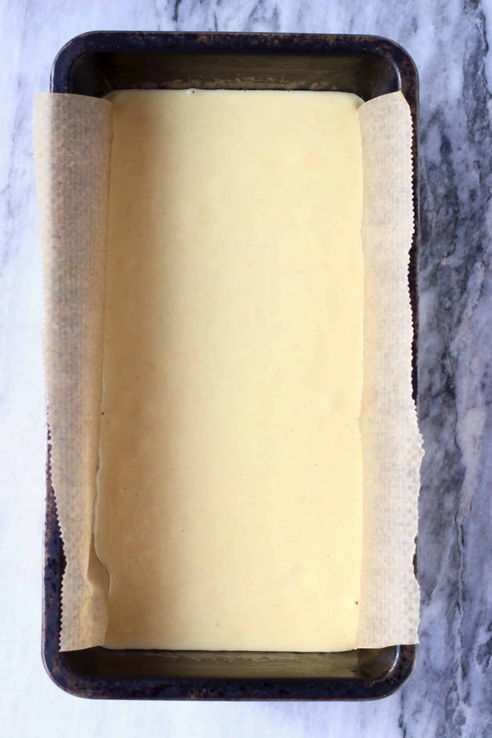 Raw gluten-free vegan bread batter in a loaf tin lined with baking paper