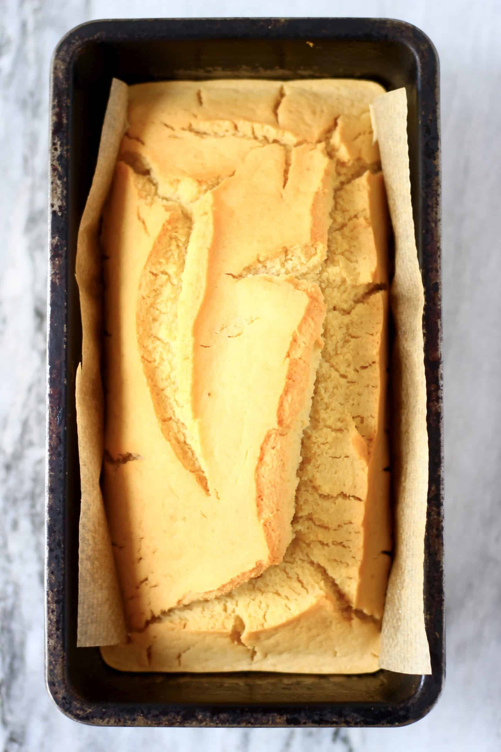 A loaf of gluten-free vegan bread in a loaf tin lined with baking paper
