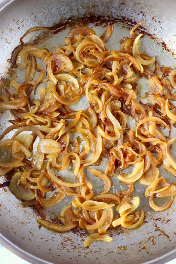 Brown caramelised onion slices in a silver frying pan