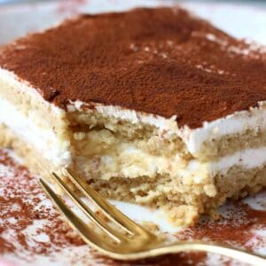 A square of gluten-free vegan tiramisu on a plate with a mouthful cut out of it