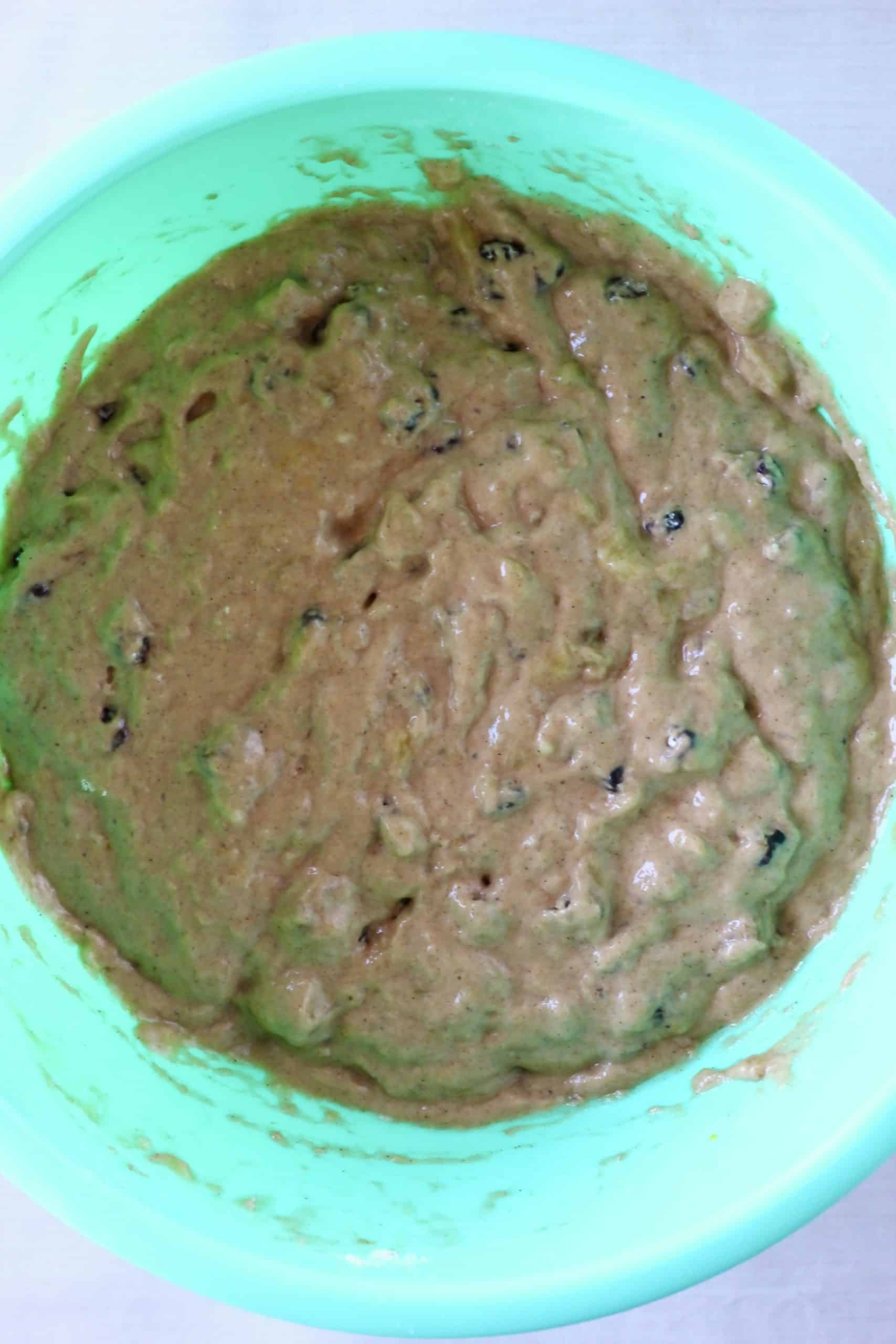 Raw gluten-free vegan banana cake batter with raisins in a mixing bowl