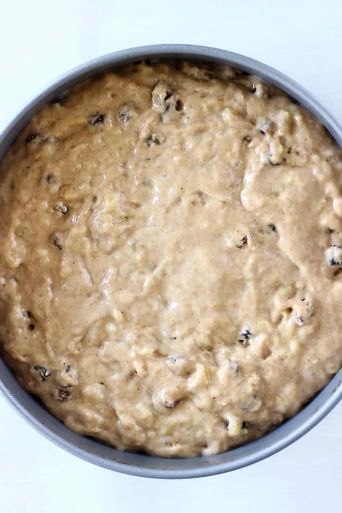 Raw banana cake batter with raisins in a round baking tin